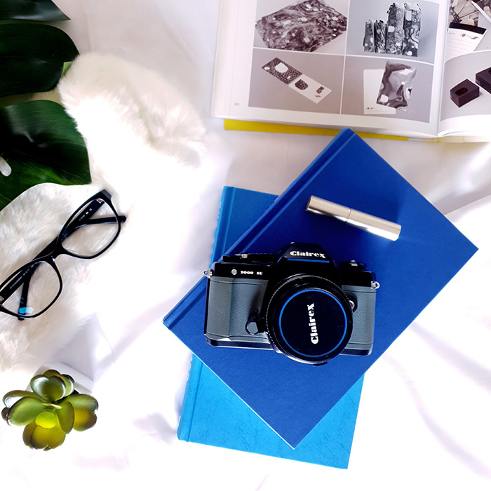 Flat lay of a camera, glasses and books for Social Media
